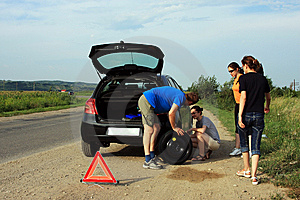 People trying to fix a flat tire