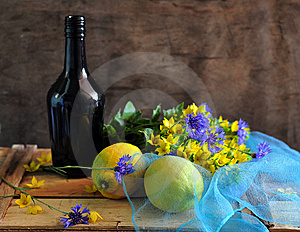 Still Life With A Bottle By Lemons And Flowers Stock Photo - Image: 15344970