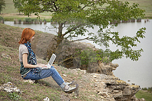 Girl With Laptop At Rock Near Lake And Tree. Royalty Free Stock Images - Image: 15403339