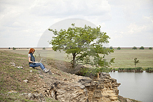 Girl With Laptop At Rock Near Lake And Tree. Royalty Free Stock Image - Image: 15403356