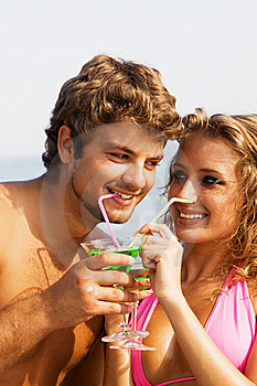 Young Couple On The Seaside With Cocktails Royalty Free Stock Photography - Image: 15421487