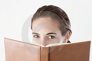Teen Girl Reading, Looking Over The Book Royalty Free Stock Photography - Image: 15495267