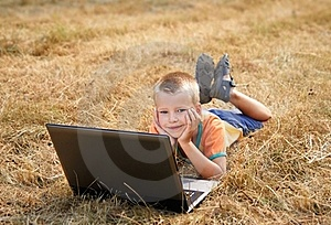 Young Boy Laying On Ground With Laptop Royalty Free Stock Photo - Image: 15583405