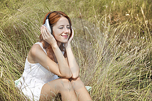 Beautiful Red-haired Girl At Grass With Headphones Royalty Free Stock Photography - Image: 15608117