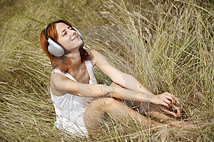 Beautiful Red-haired Girl At Grass With Headphones Royalty Free Stock Photos - Image: 15608148