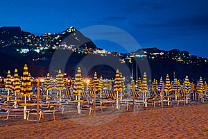 Beach At Night With An Illuminated Village Royalty Free Stock Photo - Image: 15625785