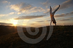 Acrobatic girl on sunset Stock Photos