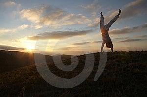 Acrobatic girl on sunset