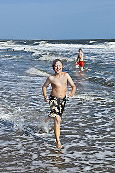 Boy Running Along The Beautiful Beach In The Waves Stock Photo - Image: 15906510