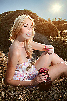 Woman Sitting On The Hay And Eat Raspberries Royalty Free Stock Photos - Image: 15921588