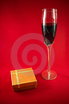 Glass Wineglass, Red Wine And Gift Box On Red Back Royalty Free Stock Photography - Image: 15945647