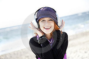 Red-haired Girl With Headphone On The Beach. Royalty Free Stock Photography - Image: 15968947