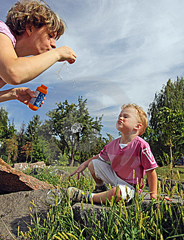 Mother And Son Blowing Soap Bubbles In A Park Royalty Free Stock Image - Image: 15970256
