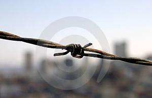 Barbed Wire In Front Of City Stock Images