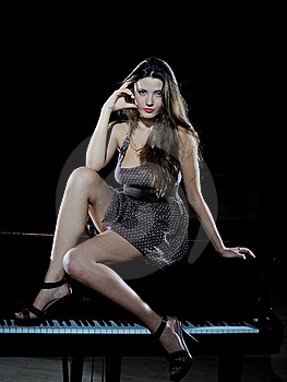 Beautiful Woman Sitting On A Black Studio Piano Stock Photo - Image: 16072100