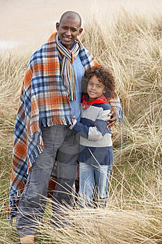 Father And Son Wrapped In Blanket Amongst Dunes On Stock Photo - Image: 16150260