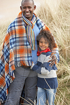 Father And Son Wrapped In Blanket Amongst Dunes On Royalty Free Stock Photo - Image: 16150355