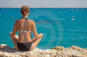 Woman In A Sarong Meditating On The Beach Royalty Free Stock Photos - Image: 16316788