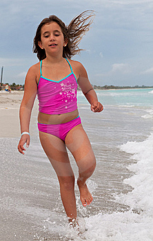 Girl On A Pink Swimsuit Running On A Beach Royalty Free Stock Photo - Image: 16388205