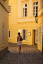 Girl walking between yellow buildings