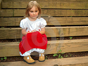 Niña en un vestido rojo, sentado en los escalones de pensamiento.