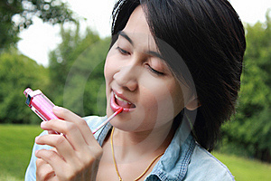 Cute Woman Looks In Mirror Also Paints Lips. Royalty Free Stock Photography - Image: 16511767