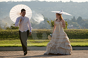 Bride And Groom Walking Outside In Sun With Umbrel Royalty Free Stock Photography - Image: 16565077