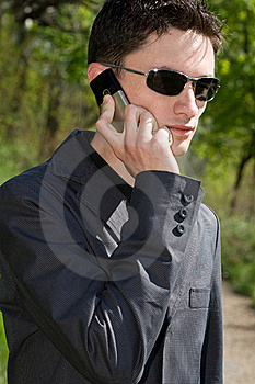 Man In Sunglasses And Jacket Talks On Cell Phone Stock Photos - Image: 16697903