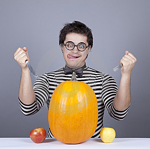 The Young Mad Men Try To Eat Apples And Pumpkin. Stock Photography - Image: 16755862