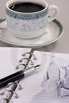 Il caffè con la carta stropicciata, penna e organizzatore.