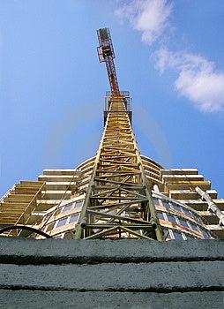 Hoher orange Kran, der ein neues Geschäftsgebäude konstruiert Stockbild