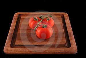 Tomatoes on cutting board Royalty Free Stock Image