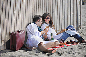 Young Couple Enjoying  Picnic On The Beach Royalty Free Stock Photo - Image: 17021325