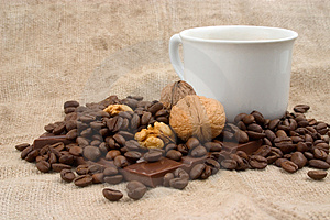 Cup of coffee, walnuts, coffee beans and chocolate