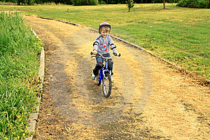 A Little Girl Rides A Bike In The Park Stock Photos - Image: 17797553