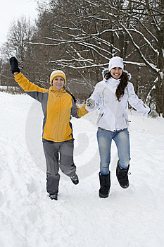 Two Joyful Women In Winter Jackets And Caps Run On Royalty Free Stock Image - Image: 17870786