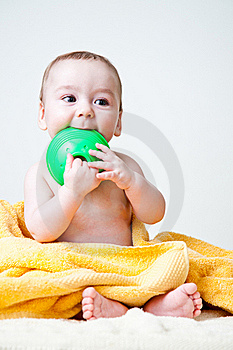 Baby Gnawing Green Toy On Yellow Towel Royalty Free Stock Photography - Image: 18014477