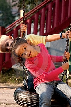 Boy And Girl On Swing Stock Image - Image: 18056211