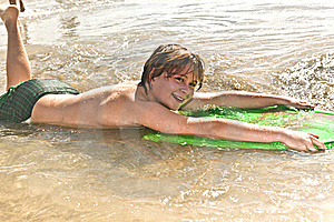 Boy Has Fun With The Surfboard Royalty Free Stock Photography - Image: 18077777