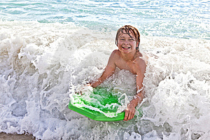 Boy Has Fun With The Surfboard Royalty Free Stock Photos - Image: 18078108