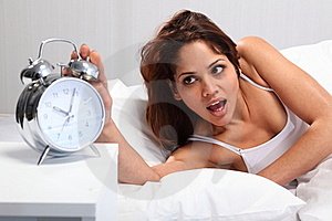Beautiful Woman Waking Up Reaching For Alarm Clock Royalty Free Stock Photos - Image: 18117268