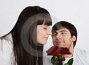 Pretty Woman Smelling Roses, Her Boyfriend Behind Royalty Free Stock Image - Image: 18221586