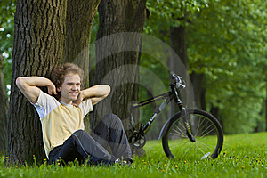 Young Man Siting Under The Tree Near His Bycicle Stock Photos - Image: 18258293