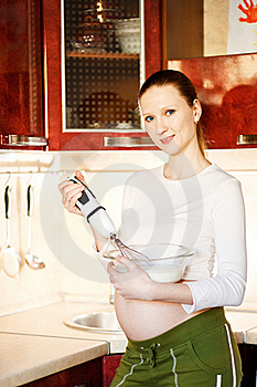 Pregnant Woman In Kitchen Making A Food And Smilin Stock Images - Image: 18435414