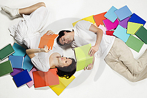 Couple Lying On Floor Reading And Looking Up. Royalty Free Stock Photos - Image: 18595998