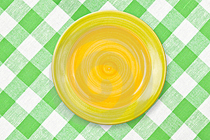 Round Yellow Plate On Green Checked Tablecloth Royalty Free Stock Photo - Image: 18667455