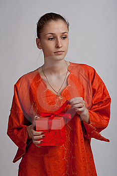 Thoughtful Girl In An Orange Dress Opens A Gift Stock Image - Image: 18686591