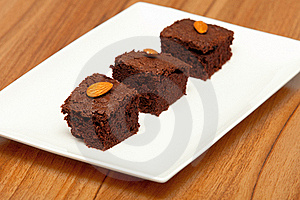 Three Brownies With Almonds On A White Plate Royalty Free Stock Photos - Image: 18693248