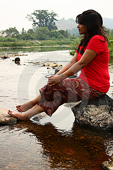 Indian Woman In Red Dress Sitting On A Rock Stock Images - Image: 18779144