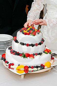 Cutting fresh wedding fruitcake Royalty Free Stock Images